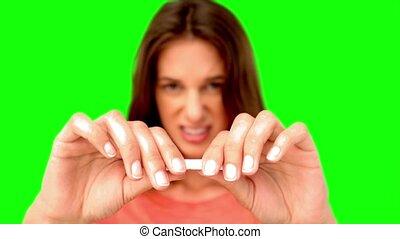 Woman breaking a cigarette on green