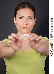 woman breaking cigarette in two