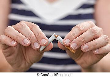 Woman breaking cigarette