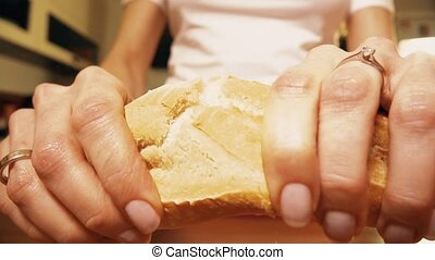 Woman breaking fresh baguette or french bread. Close-up slow...