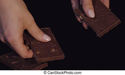 Woman breaks black chocolate bar with nuts. Close-up. Slow motion