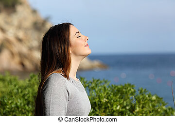 Woman breathing fresh air relaxed on vacation with the beach in the background