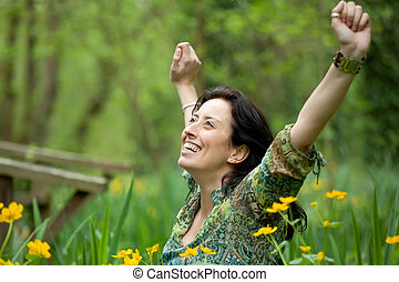 woman breathing in nature - happy woman taking a breath in...