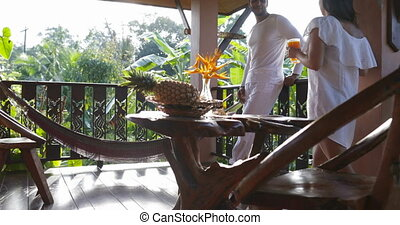 Woman Bring Juice Glass To Man Standing On Balcony, Couple...