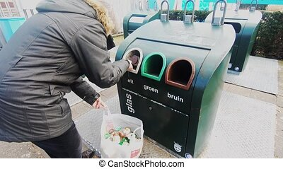 Woman brings bottles for recycling into the glass container...