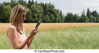 Woman browsing on mobile phone while on a walk