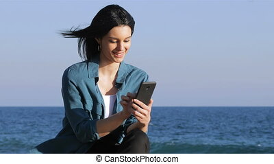 Woman browsing phone content on the beach - Serious woman...