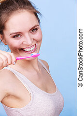 Woman brushing cleaning teeth. Girl with toothbrush. Oral hygiene. Blue background