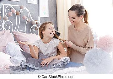 Woman brushing daughter's hair