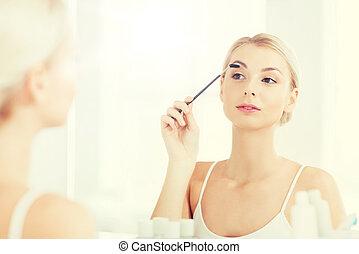 woman brushing eyebrow with brush at bathroom