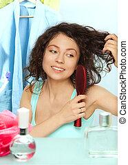 woman brushing hair in bathroom