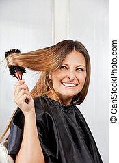 Woman Brushing Hair In Salon