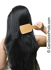 Woman brushing her black long hair - Back of young woman...