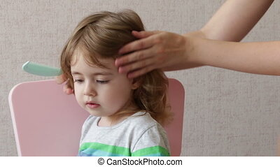 Woman brushing her daughter hair at home. Conceptual happy family