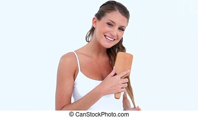 Woman brushing her hair against white background