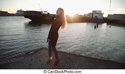 woman brushing her hair and dancing at sunset river port, Glare from the sun on the lens