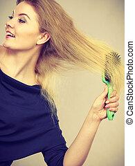 Woman brushing her long blonde hair