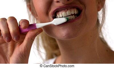 Woman brushing her teeth on white