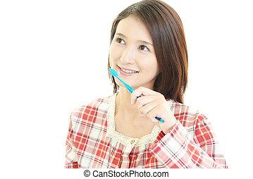 Woman brushing her teeth. - Woman sitting in pajamas smiling...