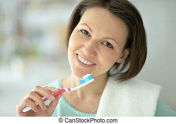 Woman brushing her teeth - Woman standing in bathroom and...