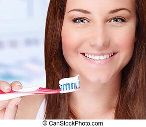 Woman brushing her teeth - Closeup portrait of beautiful...