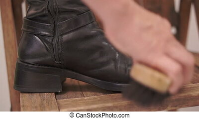 Woman Brushing High Boot Inside Leg