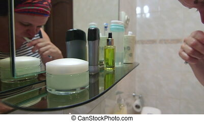 woman brushing teeth in the bathroom