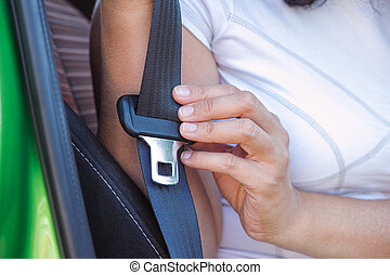 Woman buckles up the seat belt
