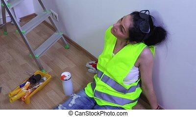 Woman builder relaxing near wall
