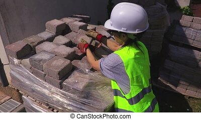 Woman builder sorting bricks at outdoor
