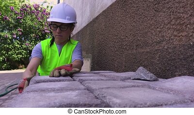 Woman builder sorting bricks near house