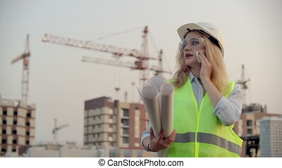Woman Builder talking on the phone with the contractor with ...