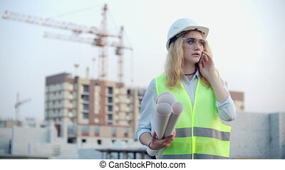 Woman Builder talking on the phone with the contractor with...