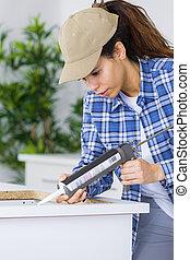 woman builder with caulking gun working in clients kitchen