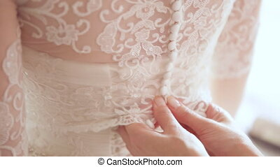Woman buttoning up wedding dress