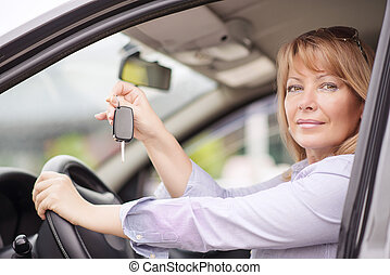 Woman buying a car - Image of happy mature woman showing key...