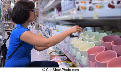 Woman buying a mug in the store - Young woman choosing a mug...