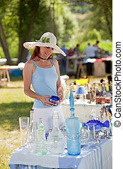 Attractive young woman in a summer sunhat buying antique collectibles at an outdoor stall at an open-air fair or market, browsing through glassware on a table in a park in Provence, France.