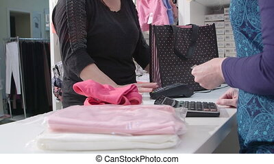 Woman buying clothes using credit card for payment in baby and maternity shop