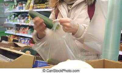 Woman buying cucumber and vegetables in delicatessen