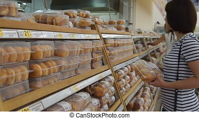 Woman buying donuts in the pastry section
