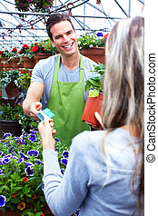 Woman buying flowers at a flower shop.