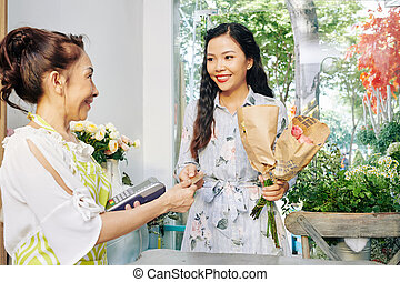 Woman buying flowers in shop
