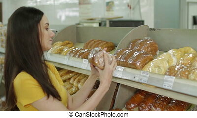 Woman buying fresh bread in in grocery store