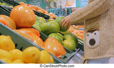 Woman buying fresh exotic citrus fruits at grocery store