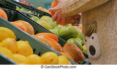 Woman buying fresh exotic citrus fruits at grocery store -...
