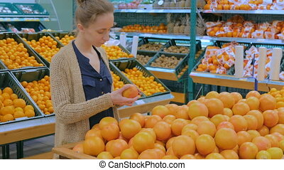 Woman buying fresh grapefruits at grocery store