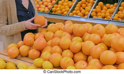 Woman buying fresh grapefruits at grocery store - Woman...