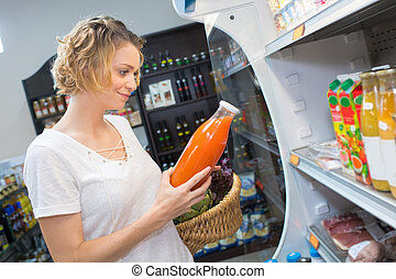 woman buying fresh juice at the grocery store
