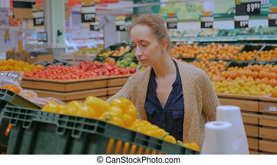 Woman buying fresh orange bell peppers at grocery store